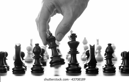 Chess move with hand picking up the queen black and white
