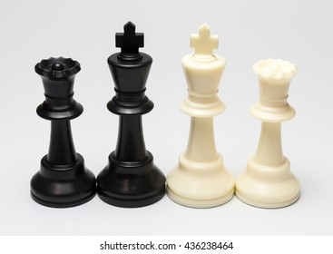 Chess pieces black and white kings and queens isolated on white background