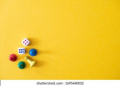 Chess pieces, game chips, Lotto barrels, draughts and playing cubes laid on a yellow background: entertainment, games at home for the whole family, the concept of table games. Board game. Board games