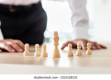 Chess pieces of king and pawns placed on office desk with king as the leader and businessman in background in a conceptual image.