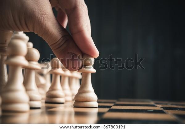 Schachfiguren auf dem Brett. schwarzer Holzhintergrund.