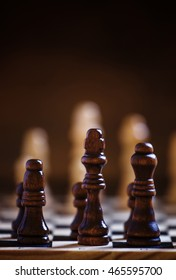 Chess pieces on the board, intellectual game, dark brown background, selective focus
