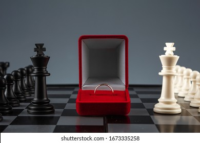 Chess pieces on a chessboard and a box with a golden ring, game. The concept of confrontation, career, competition, startup, truce, marriage, partnership