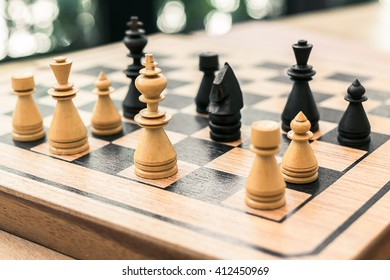 Chess pieces on chessboard in the room