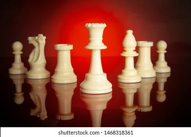 Chess pieces on dark background with red backlight close up