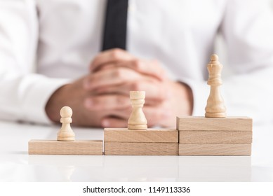 Chess pieces on stacked stepped wooden blocks with a businessman seated behind conceptual of corporate and business success.