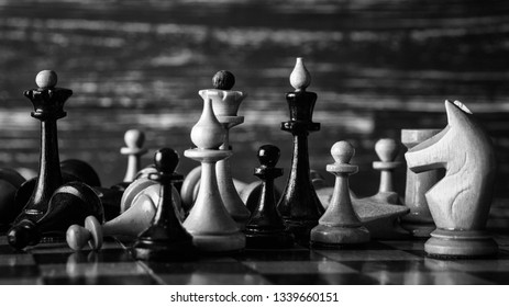 Chess pieces on a wooden chessboard against a dark background. Black and white photography