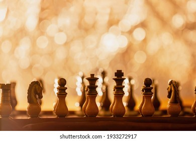 Chess pieces placed on chess board, beginning of game. Abstract shining background with bokeh