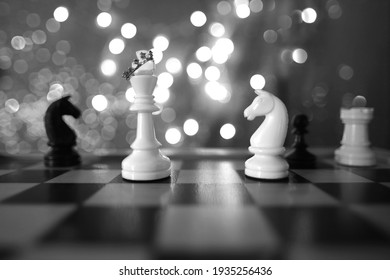 chess pieces, queen in crown white and black on a chessboard, concept of leadership and teamwork in business, duel, opposition of light and dark forces, sports game