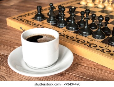 Chess pieces ready for game on the table and a cup of coffee
