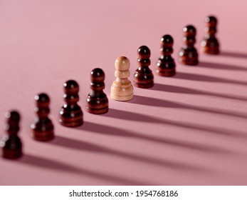chess pieces in a row, pawns on a pink background, team concept