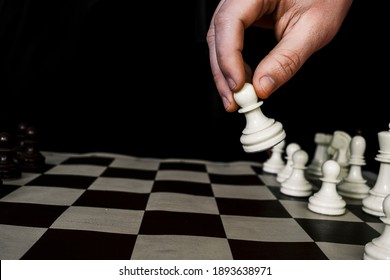 Chess player hand makes a move, selective focus