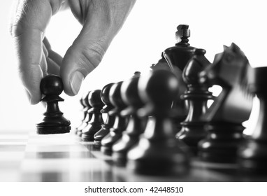 chess  player hand moves pawn selective focus black and white