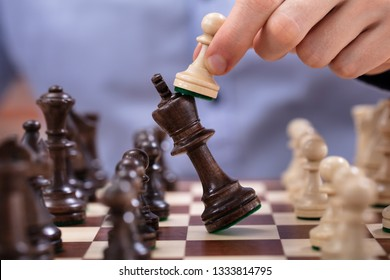Chess Player Makes A Move To Defeat King Piece