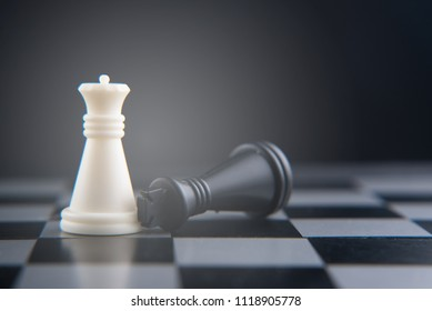 chess set on chess board. fallen black king on white queen. women power concept. selective and soft focus