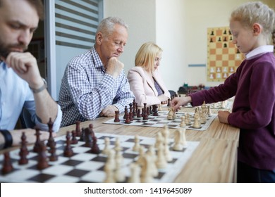 Chess tournament at chess club where adult teachers play chess with their school students