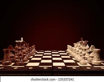 Chessboard with chess pieces, board game on brown background