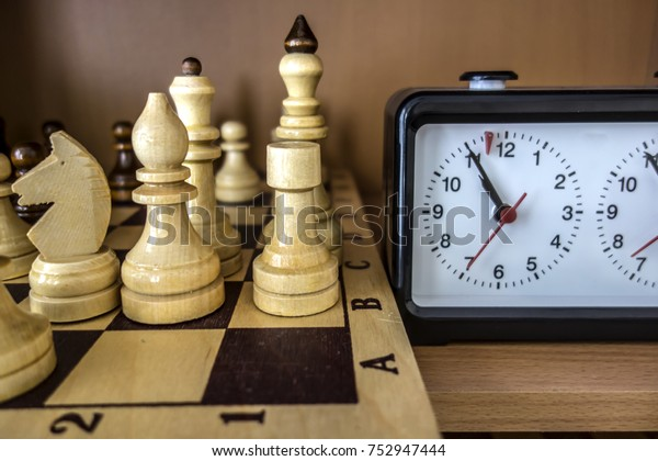 Chessboard, chess pieces and chess clock closeup. In the picture there are made of wood king, queen, horse, officer and rook.