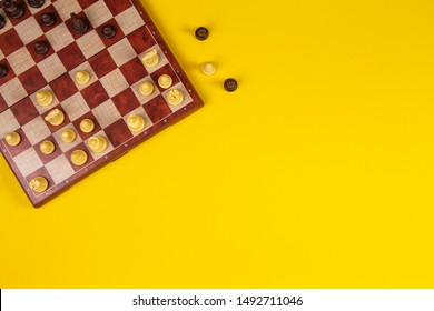 Chessboard with chesses on yellow background, top view