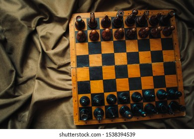 a chessboard lies on a crumpled brown cloth, chess pieces on a chessboard, the beginning of a game, vintage chess, old chess, of chess