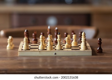 Chessboard on table in game process. Board with chess pieces. Strategic set of wooden figures during break or finish of battle. Boardgame close up. Business strategy, tactics, tournament concept