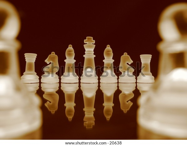 Chessmen in a row in bright sepia.