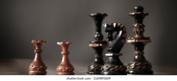 Chessmen. Two white pawns against the black figures of the king and queen.