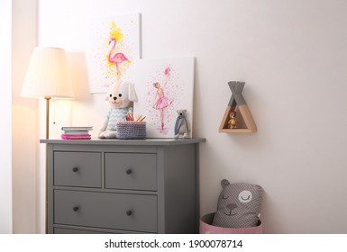 Chest of drawers and beautiful pictures in children's room. Interior design