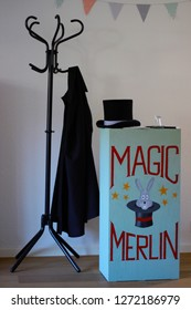 Chest of drawers containing magic tricks (self-painted, no copyright), stovepipe hat, magic wand and magic coat. Equipment for a magician on stage.