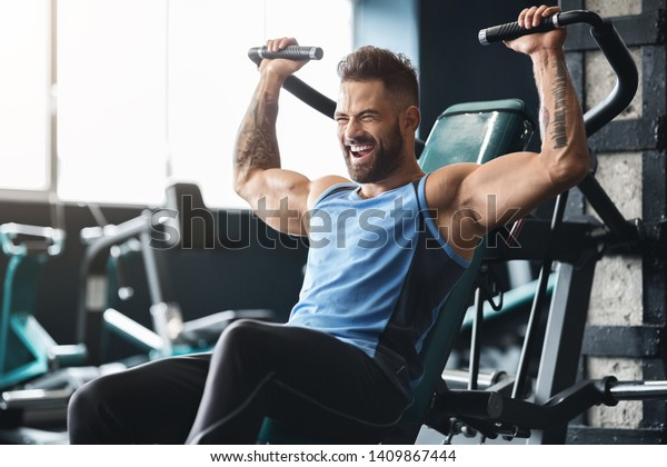 Chest exercise. Handsome muscular man working out hard at gym, free space