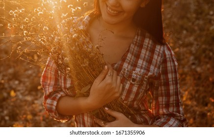 The chest and lower part of the face of the laughing woman holds a large bouquet of wild flowers. Backlit Girl Smiling and holding bunch of wildflowers, vintage colorized image
