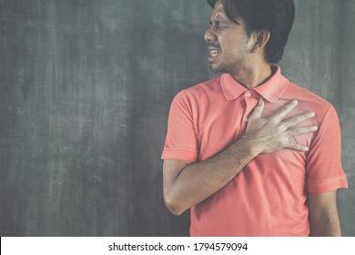 Chest pain, Young asian man having heart attack on Cement wall background with copy space, Problems and health care concepts
