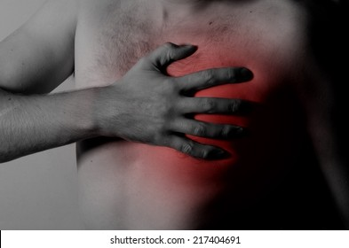 Chest Pain Young man holding hand to spot chest pain