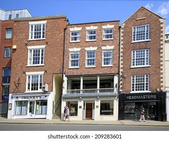CHESTER, CHESHIRE - AUGUST 4, 2014: Shop frontages. Chester has a number of medieval buildings, but some of the black-and-white buildings within the city centre are Victorian restorations
