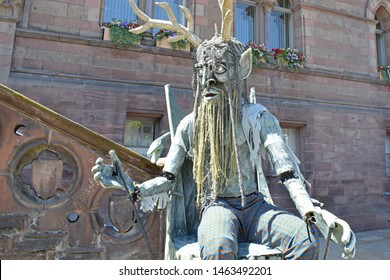 Chester, Cheshire, UK. June 24, 2018. Chester Midsummer Watch Parade. Giant green man with horns and beard is operated as a puppet. Seated outside Chester Town Hall in front of stone steps