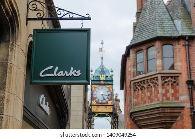 Chester, Cheshire / United Kingdom - May 25 2019: Clarks shoes company logo sign and the famous Chester Eastgate Clock at the background. The picture is taken at the Chester High Street.