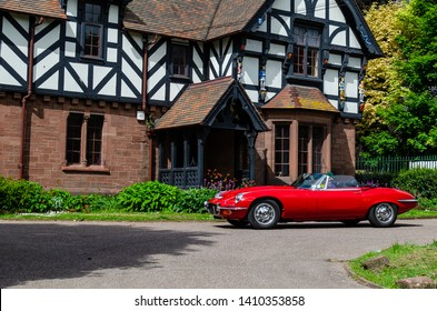 "Chester, Cheshire / United Kingdom - May 25 2019: ""Brums and Buns"" retro cars festival at Chester UK. The red Classic Jaguar E-type Series sport car passing by the beautiful english Tudor style house."