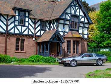 "Chester, Cheshire / United Kingdom - May 25 2019: The classic DMC DeLorean car passing by a beautiful english Tudor style house called the Lodge. ""Brums and Buns"" retro cars festival at Chester."