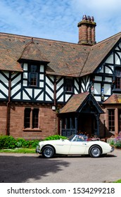 "Chester, Cheshire / United Kingdom - May 25 2019: ""Brums and Buns"" retro cars festival at Chester UK. White 1960 Austin Healey 3000 Mk I car passing by the beautiful English Tudor style house."