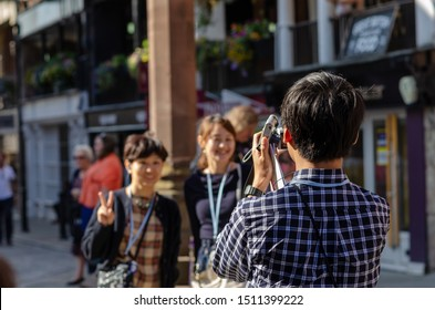 Chester, Cheshire / United Kingdom - September 21 2019: Young tourist from China taking photo of two smiling asian girls in the street of Chester, holding two photo cameras in his hand.