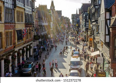 Chester, Cheshire / United Kingdom - September 21 2019: Iconic Eastgate street in Chester with traditional Tudor style house and people having a walk. The sun rays in photo create a special atmosphere