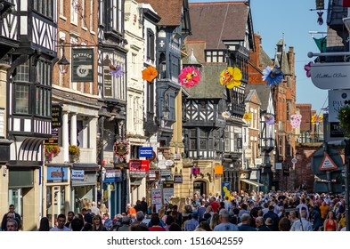 Chester, Cheshire / United Kingdom - September 21 2019: Iconic Eastgate street in Chester with traditional Tudor style houses, high street shops and a lot of people having a walk.