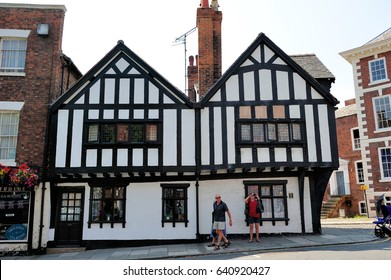 CHESTER, ENGLAND- JULY 17, 2013: Undefined people and City Centre shopping in Tudor style historic centre of Chester. This city is in north-west England, founded as a Roman fortress in the 1st century
