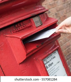 Chester, UK, 05 February 2015: A female hand is posting a letter in a mail box belonging to Royal Mail
