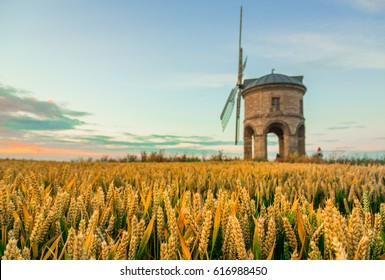 Chesterton Windmill, a 17th-century cylindrical stone tower mill with an arched base, beneath a wheat field, in Warwickshire, West Midlands, UK.