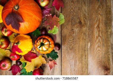 Chestnut, apples, pumpkins and yellow gourd with colorful maple leaves, copy space. Thanksgiving or fall greeting background