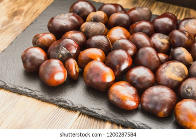 chestnut fruits are located on a slate dish lying on a wooden table