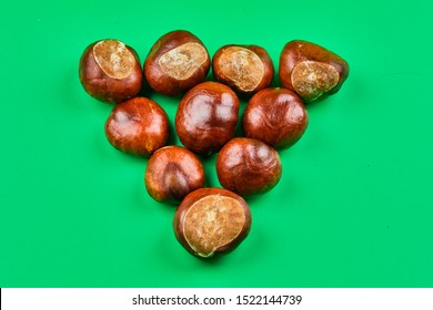 Chestnut seeds set to figure inverted pyramid on green background