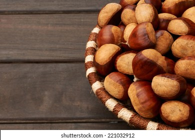 chestnuts in a  basket with wooden planks on the left