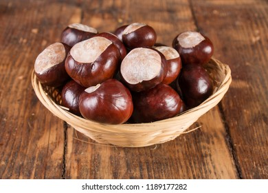 Chestnuts in beautiful retro basket on wooden desk. Autumn concept background. Close up, selective focus